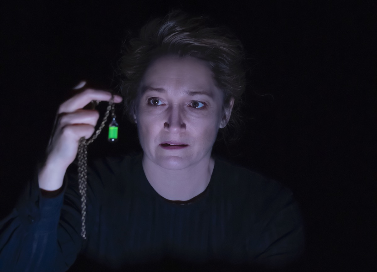 an actress playing marie curie holds a green glowing vial that represents radium