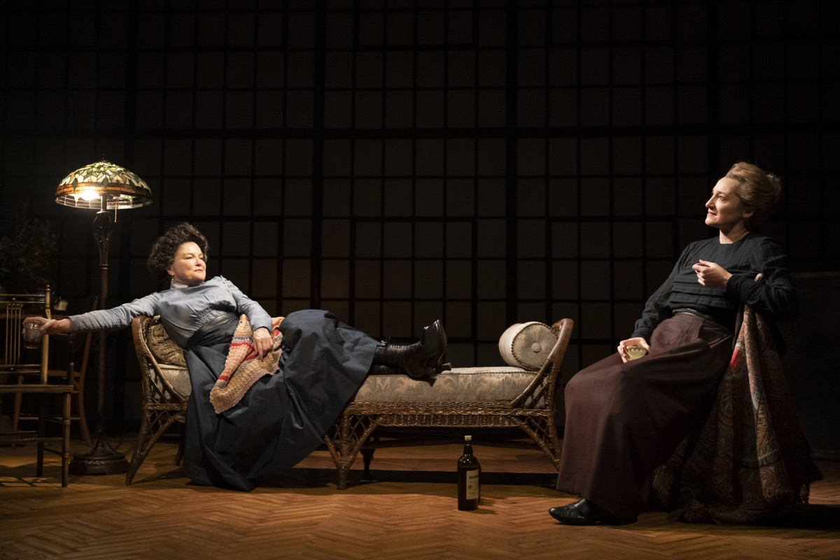 two women sit on chairs happily on stage