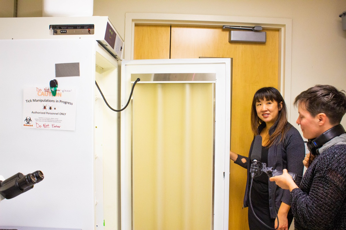 """a large fridge with a sign that reads """"caution tick manipulation in progress"""" while a woman opens the door, and another woman interviews her with a microphone"""