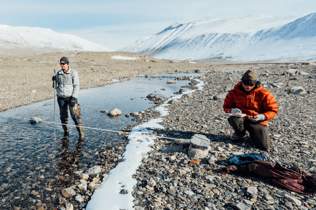 two researchers, one in a shallow river and the other on the side, taking measurements
