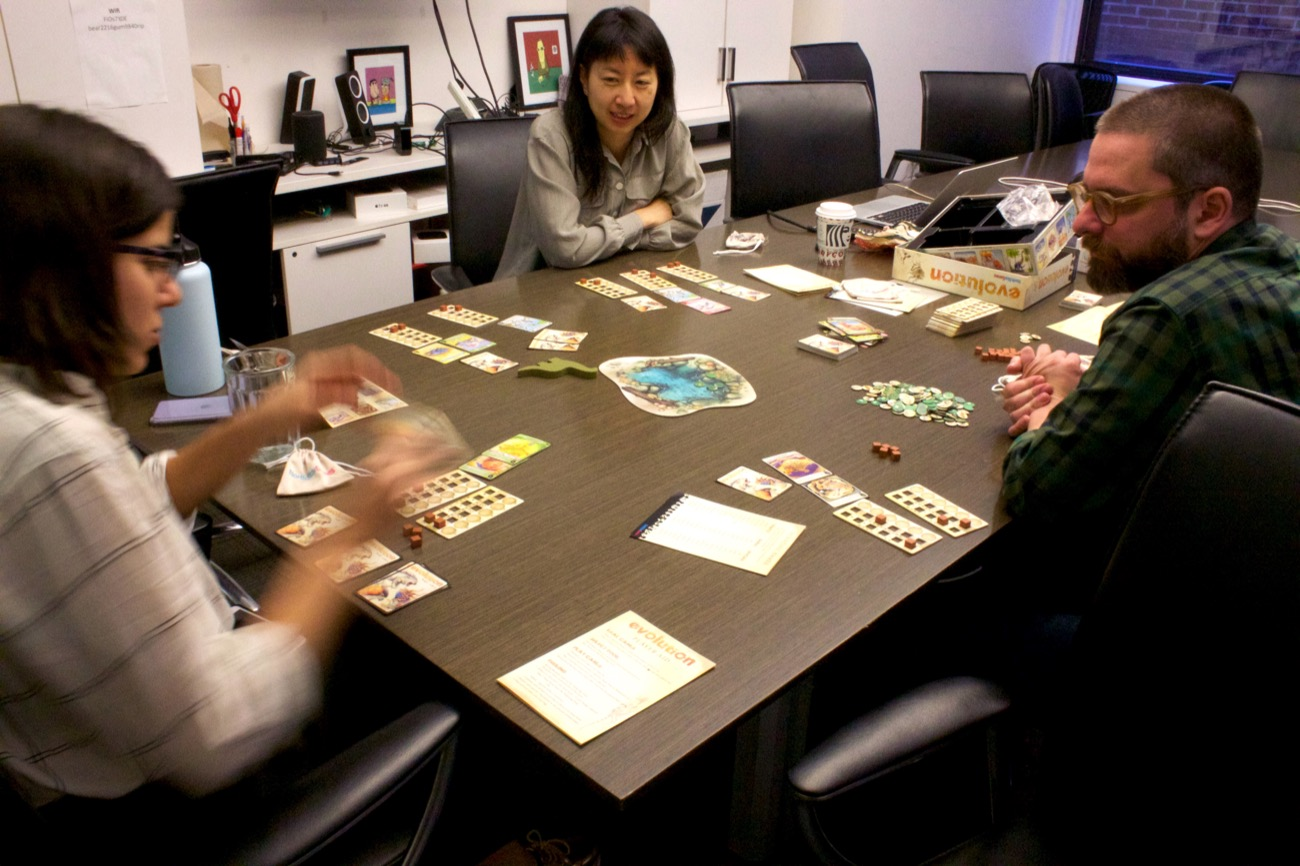 three people sitting at a table with cards playing a board game