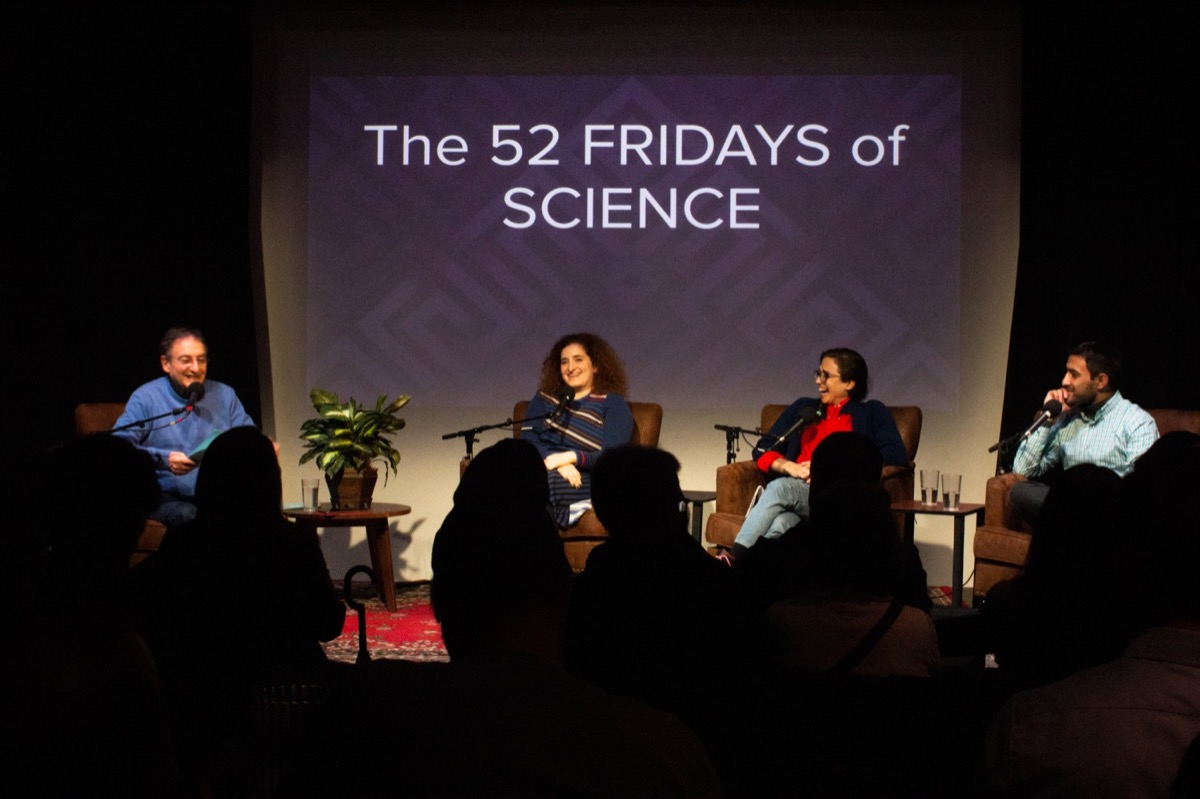"four people on stage in an interview with a slide in the background that reads ""the 52 fridays of science"""
