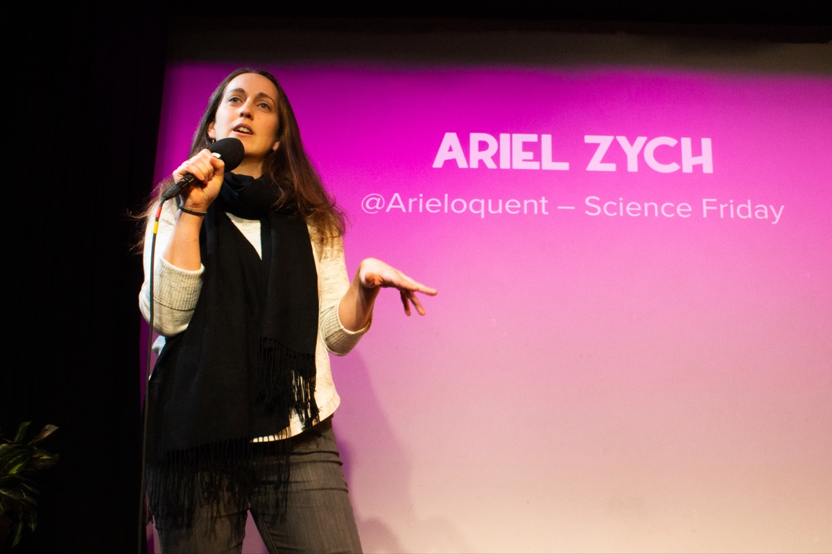 woman on stage with a microphone, with the name 'ariel zych' projected on a pink-tinted projection screen behind her