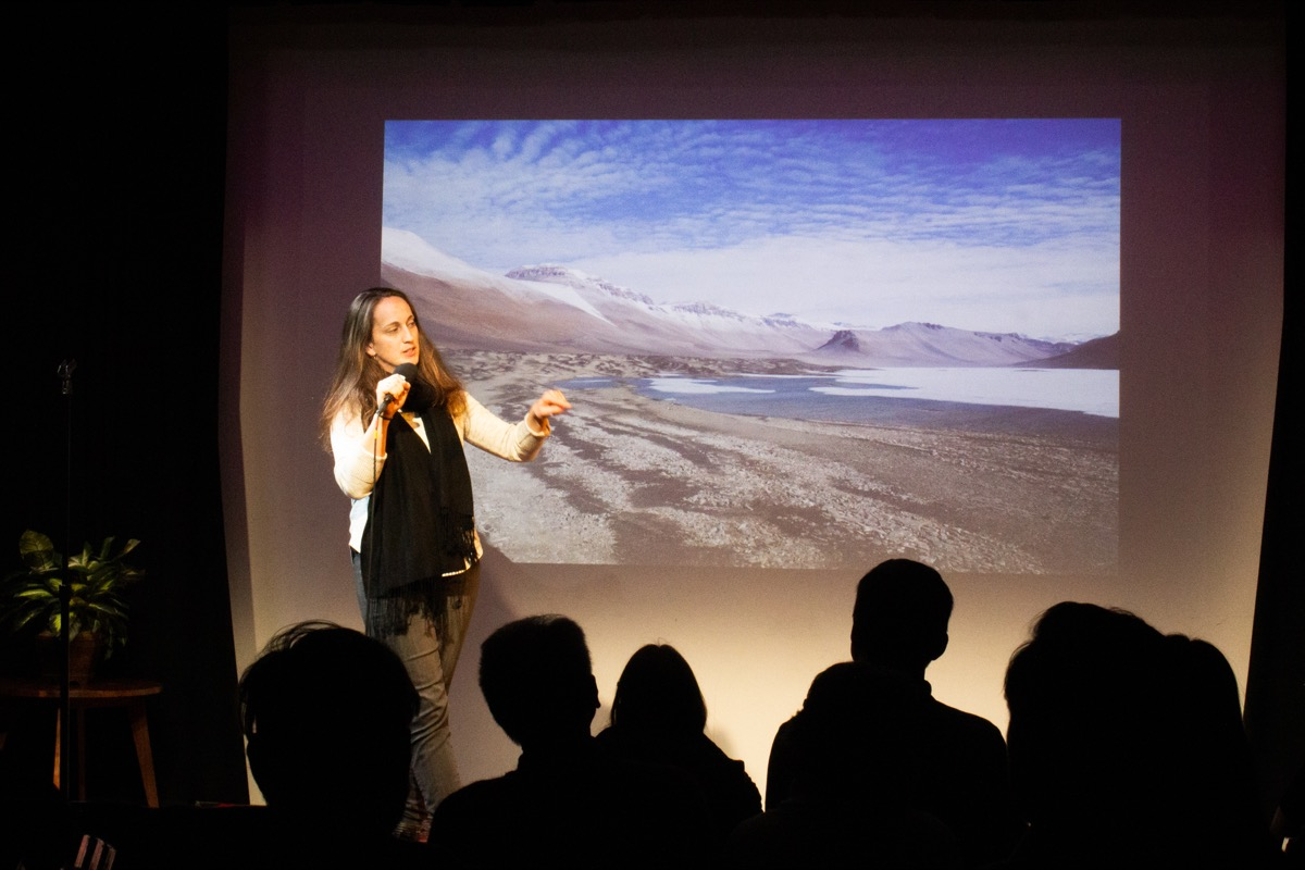 woman with a microphone on stage, with an image of an antarctic landscape behind her, in front of a seated crowd