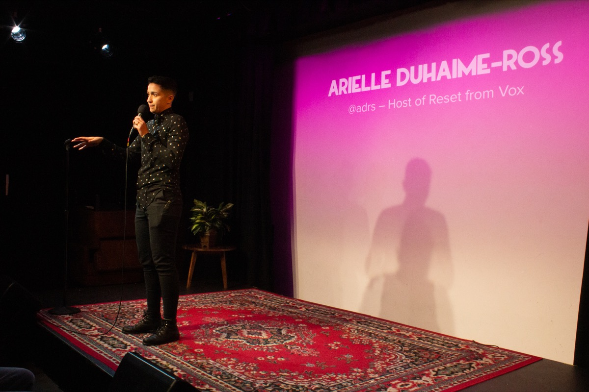 woman with a microphone on stage, with the name 'arielle duhaime-ross' projected on a pink-tinted projection screen behind her