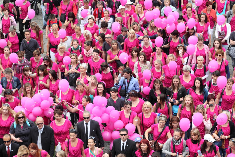 dozens of people in pink t-shirts with pink balloons