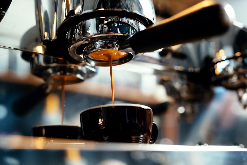 an espresso machine dripping espresso into a cup