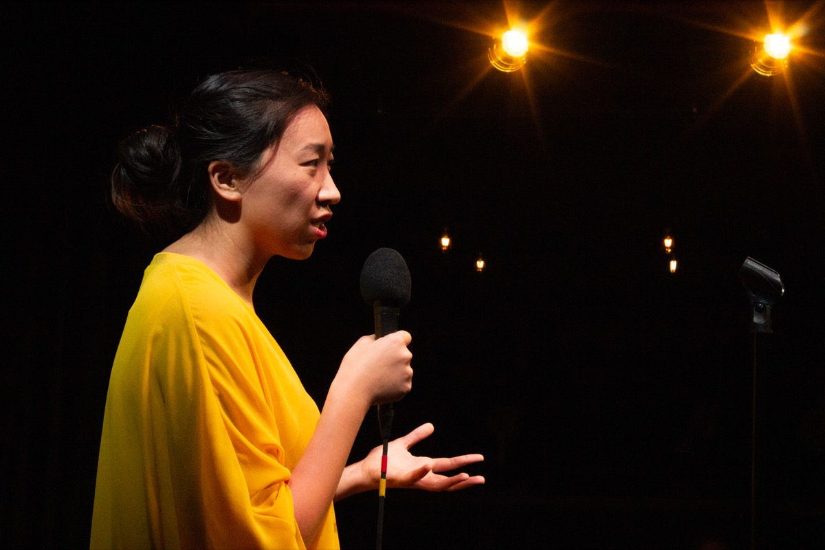 woman in a yellow shirt with a microphone, looking inquisitively and gesturing openly with her left hand toward the crowd