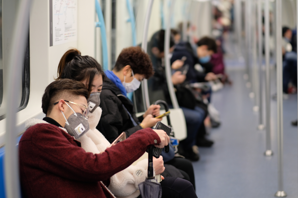 people in china on a subway train. everyone is wearing medical masks