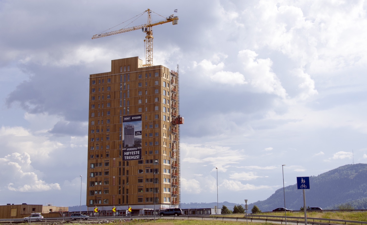 An 18-story tall wood building with a crane above it