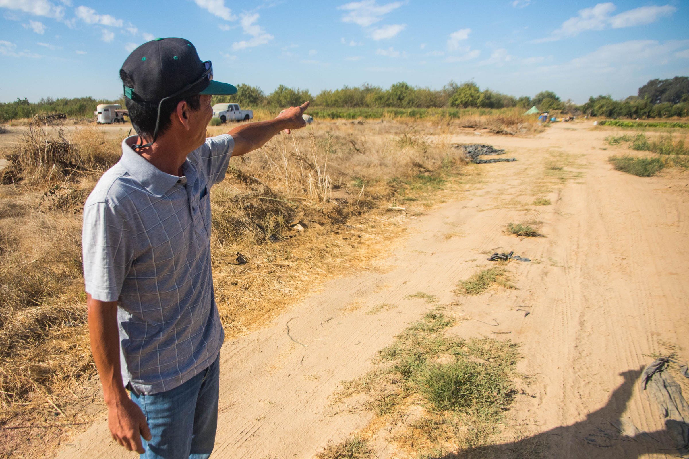 a man points off in the distance in a dirt farm