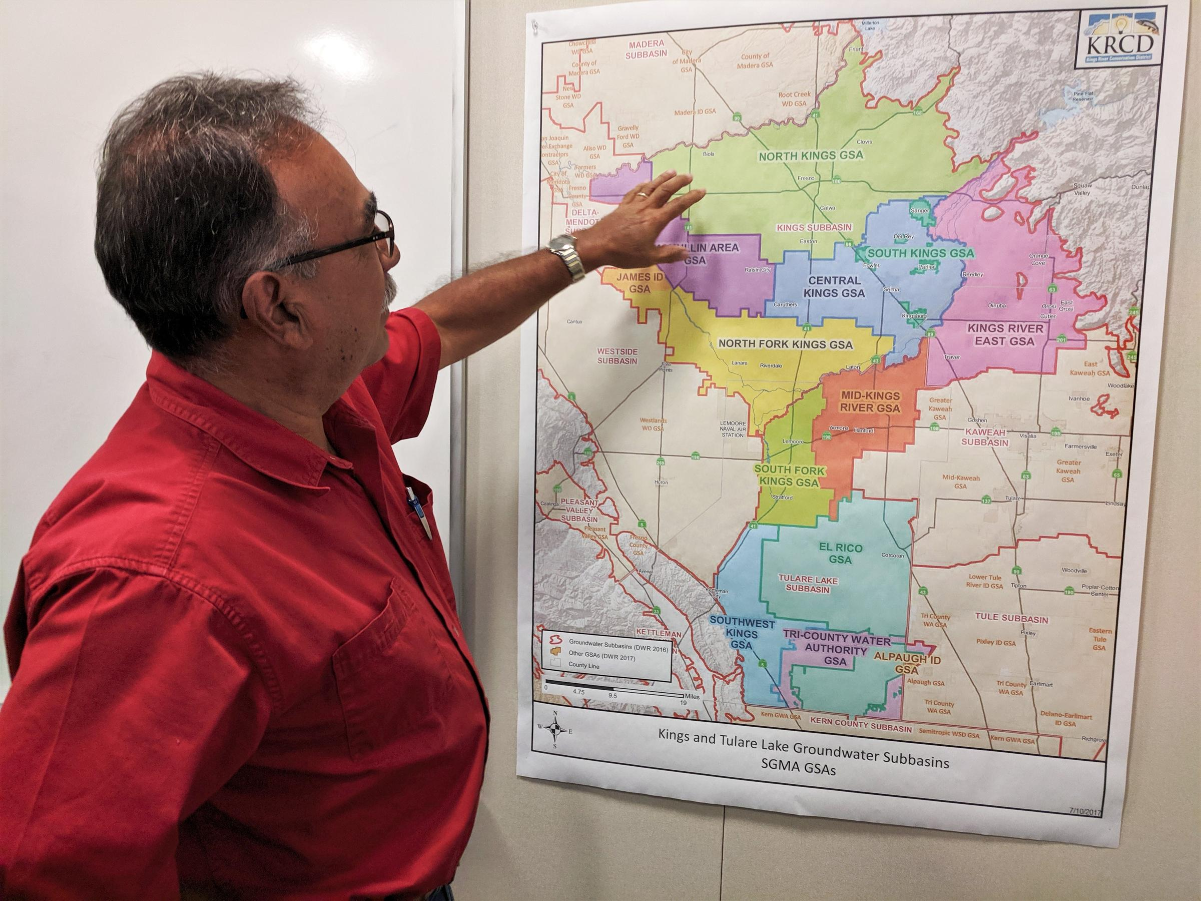 a man gestures to a colored map