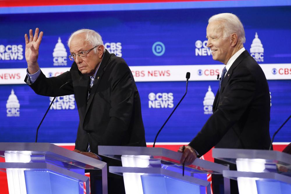 bernie sanders, raising his hand, on a debate stage with joe biden