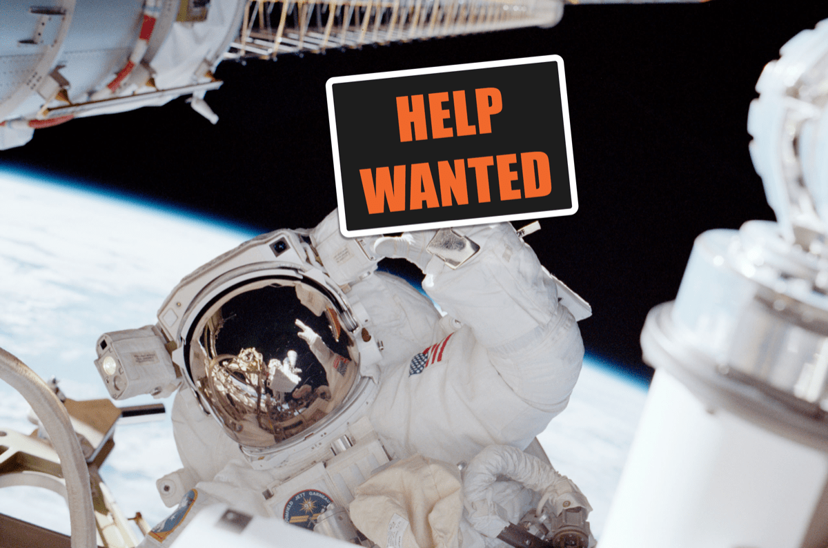 """an astronaut in space on the international space station holds a photoshopped sign that says """"help wanted"""""""