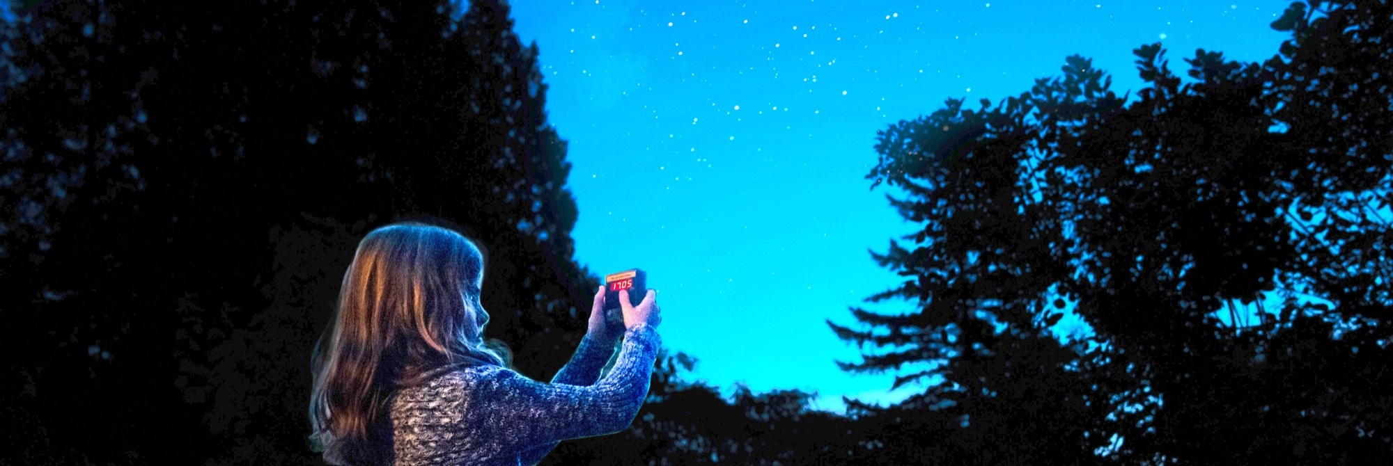 a girl holding up a device at night with dark trees and stars in the background