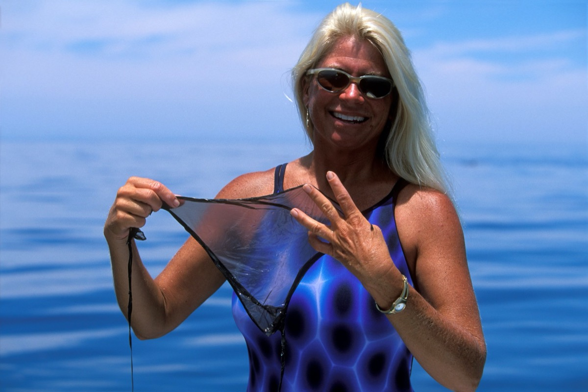 a woman holds up a blackish gray transparent membrane that is shedded whale skin