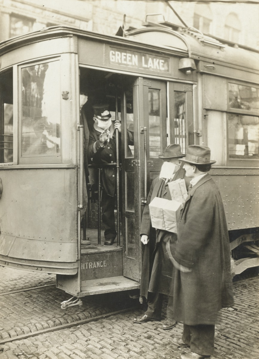 a street car conductor wearing a face mask stops a passenger from trying board who wasn't also wearing a mask