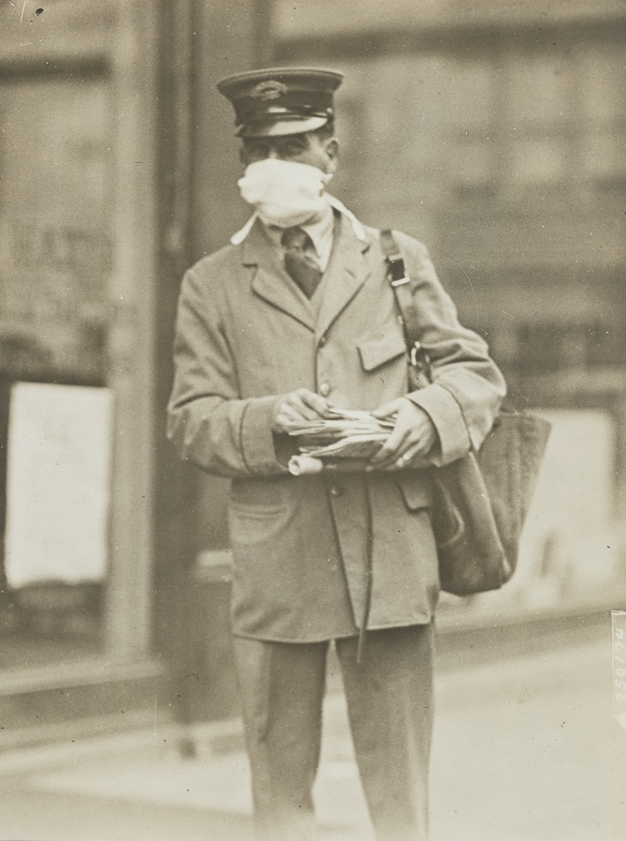 a black and white photo of a man in a flat cap and coat and a bag of mail. he wears a face mask