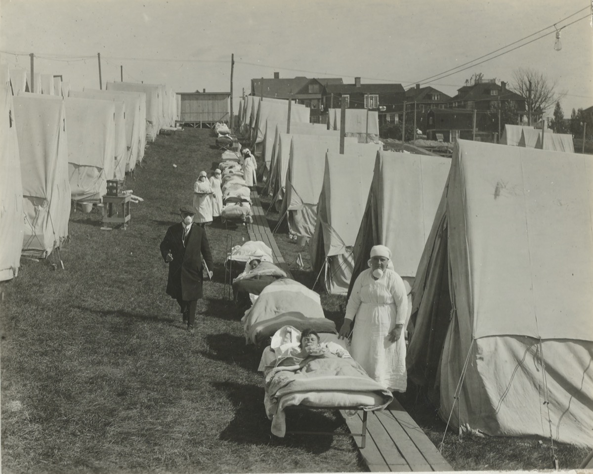 rows of white tents with beds and patients lying outside. nurses come by to check on them. in the background you can make out nearby homes
