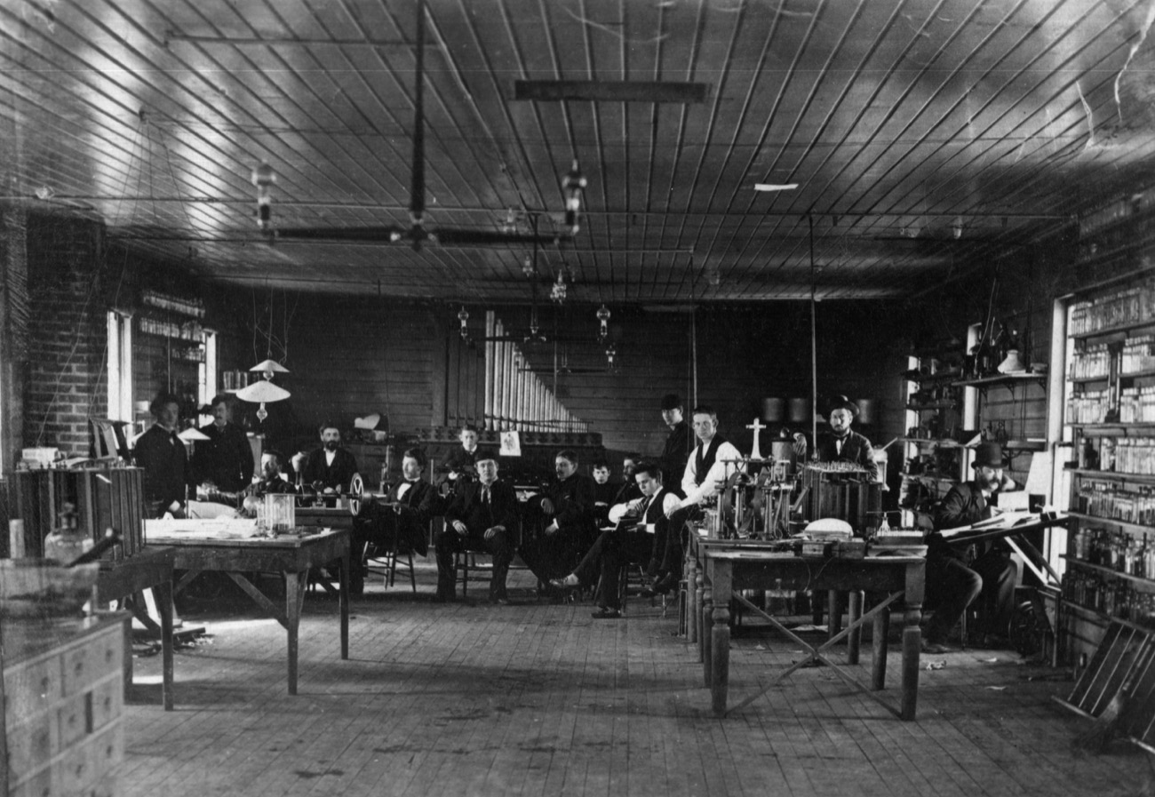 a black and white photo of a group of over a dozen people in a room with lightbulbs and chairs and tables