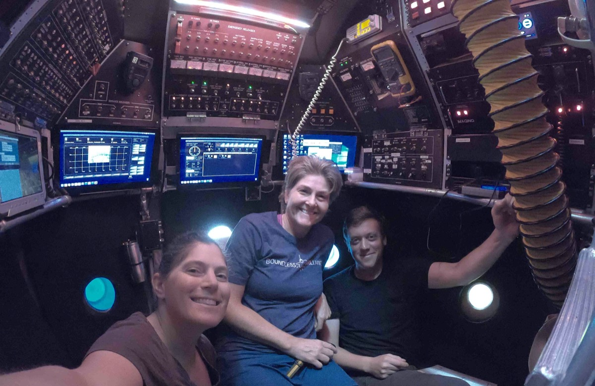 two women scientists and a man sit inside a submarine with a lot of buttons and screens, taking a selfie
