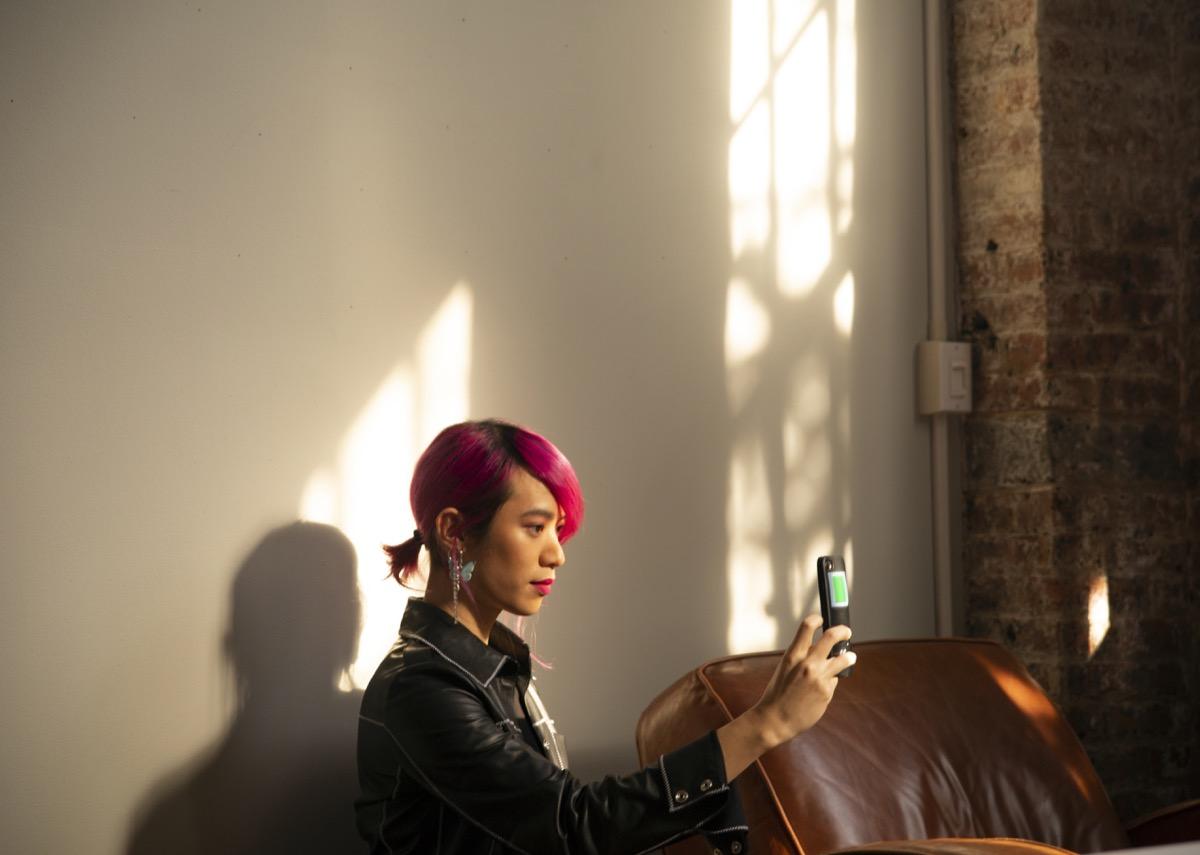 A non-binary femme using their phone.