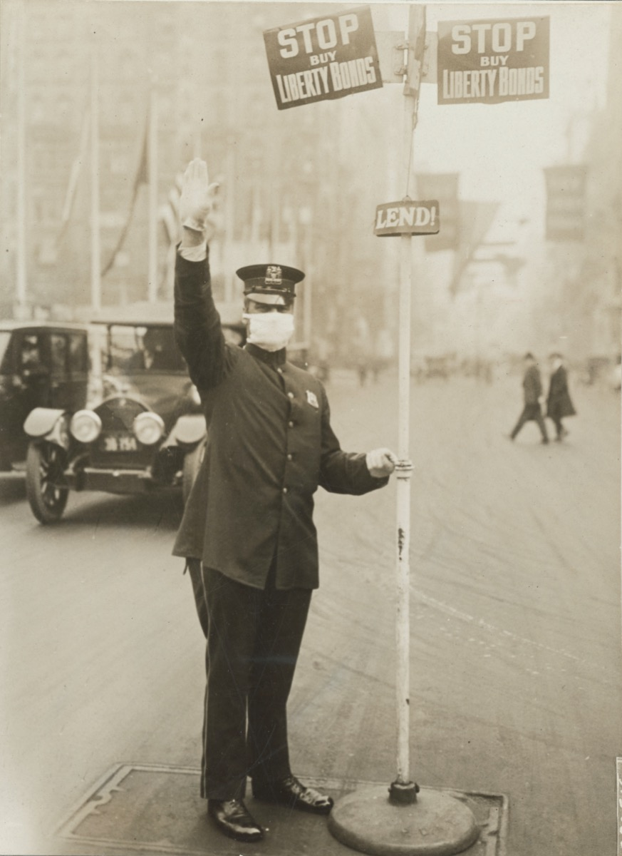 a man in a flat cap, white gloves, and face masks, directs car traffic