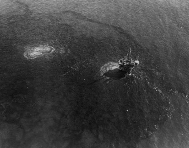 a black and white photo of an offshore oil rig seen from above, where you can see black oil bubbling and expanding out from the rig beneath the ocean