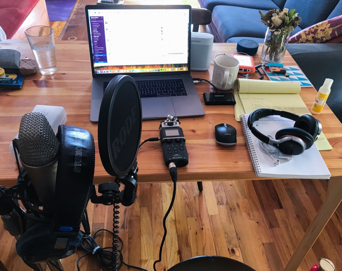 a wooden table at an apartment with a laptop, headphones, note pad, and an audio recorder. close up is a mic on a stand