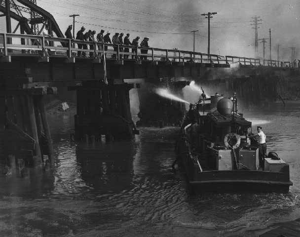a boat on a river trying to put out a fire on the river. people watch on a bridge overhead