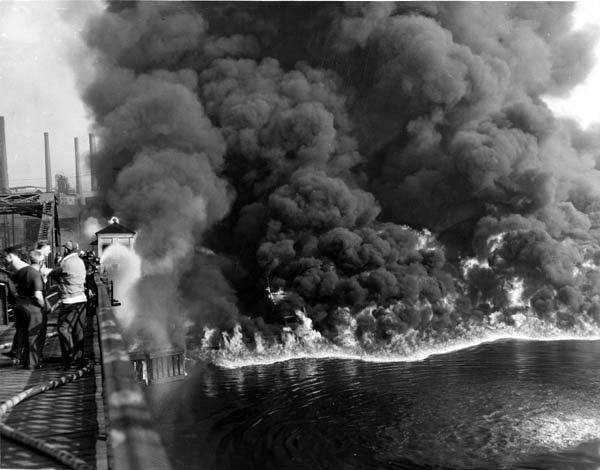 large black clouds of smoke tower above a river on fire. people stand on a bridge with water hoses trying to control the fire