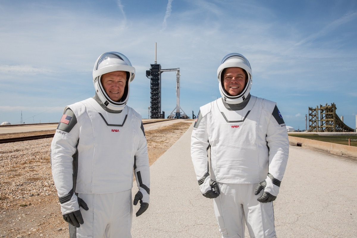 two men in space suit, flight gear on a landing pad. in the background is a rocket