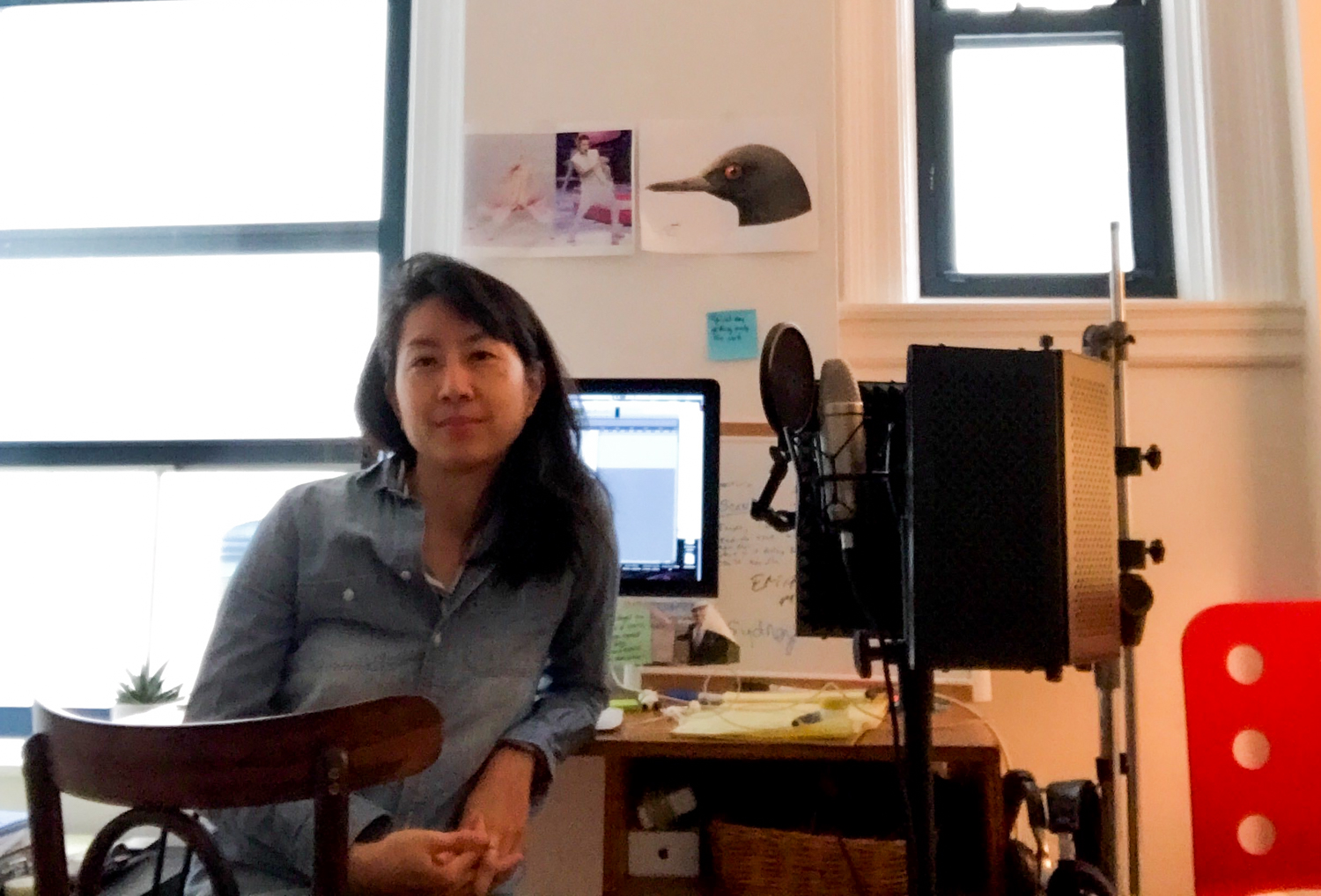 an asian woman sits at a desk at home with a mic stand and microphone next to her