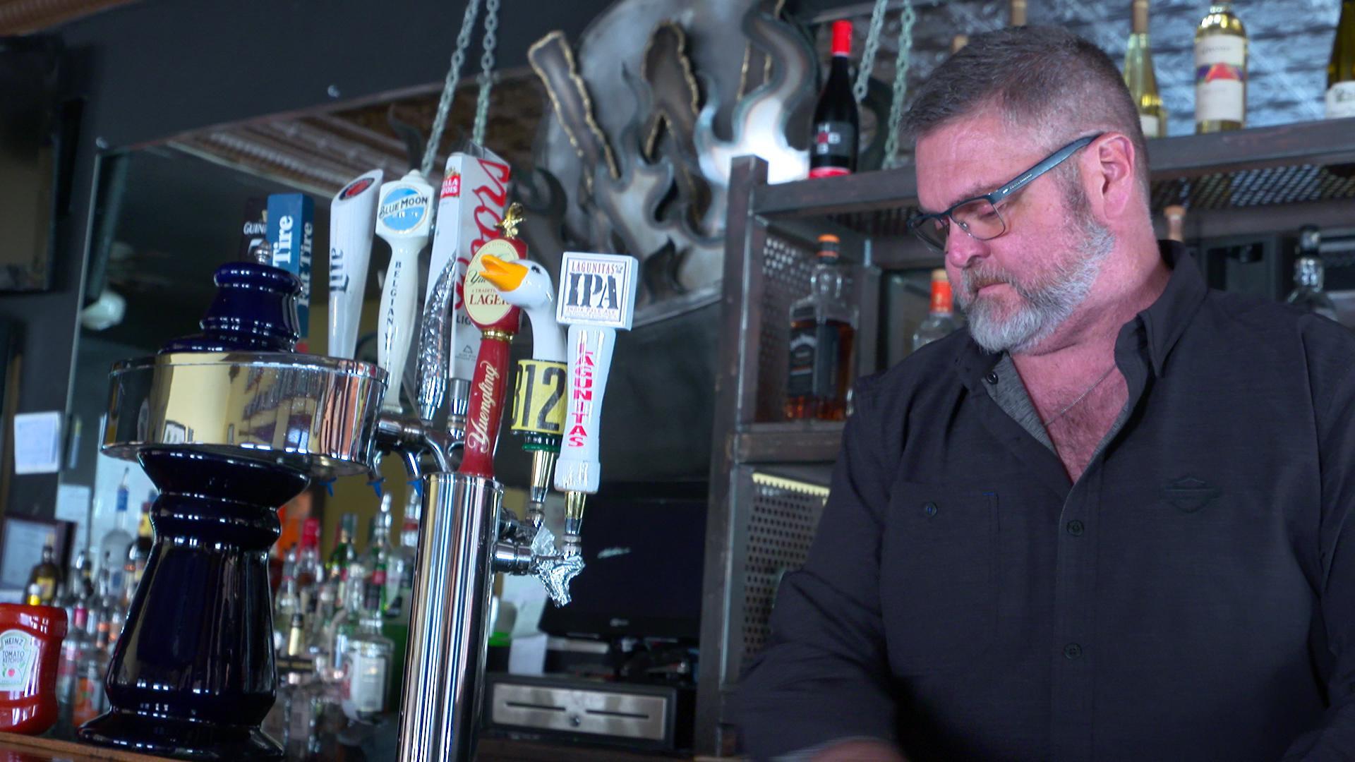 a man looking solemn behind a bar
