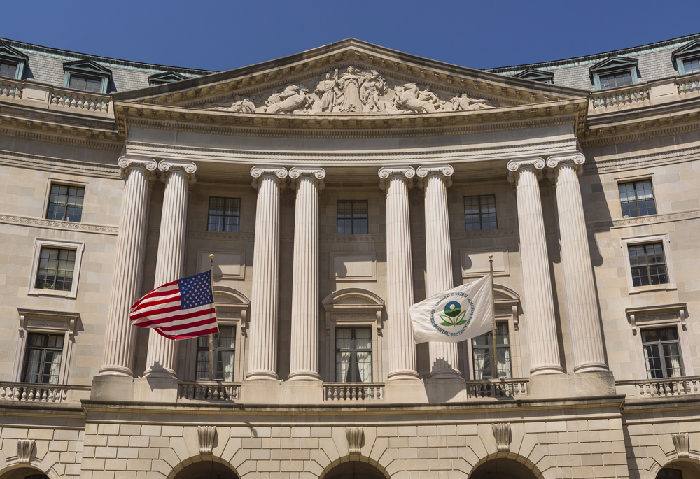 a white stone building with large pillars and an american flag and a white flag that shows the symbol of the environmental protection agency