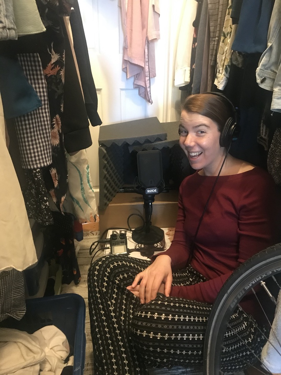 a woman sits in a closet with headphones speaking into a microphone propped on a box surrounded by foam blocks