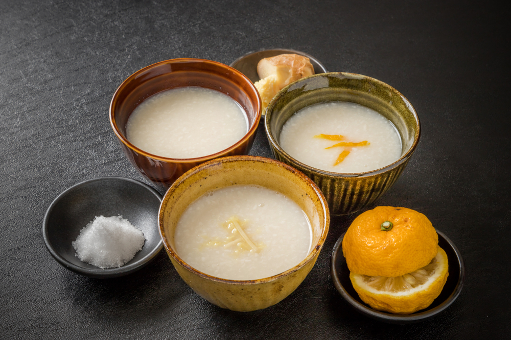 three bowls of a white liquid, with a smaller bowl of salt and another with an orange