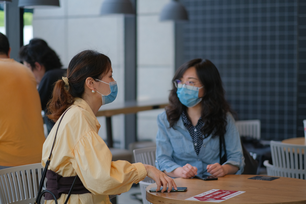young women talking in cafe, wearing surgical mask to prevent infection of coronavirus