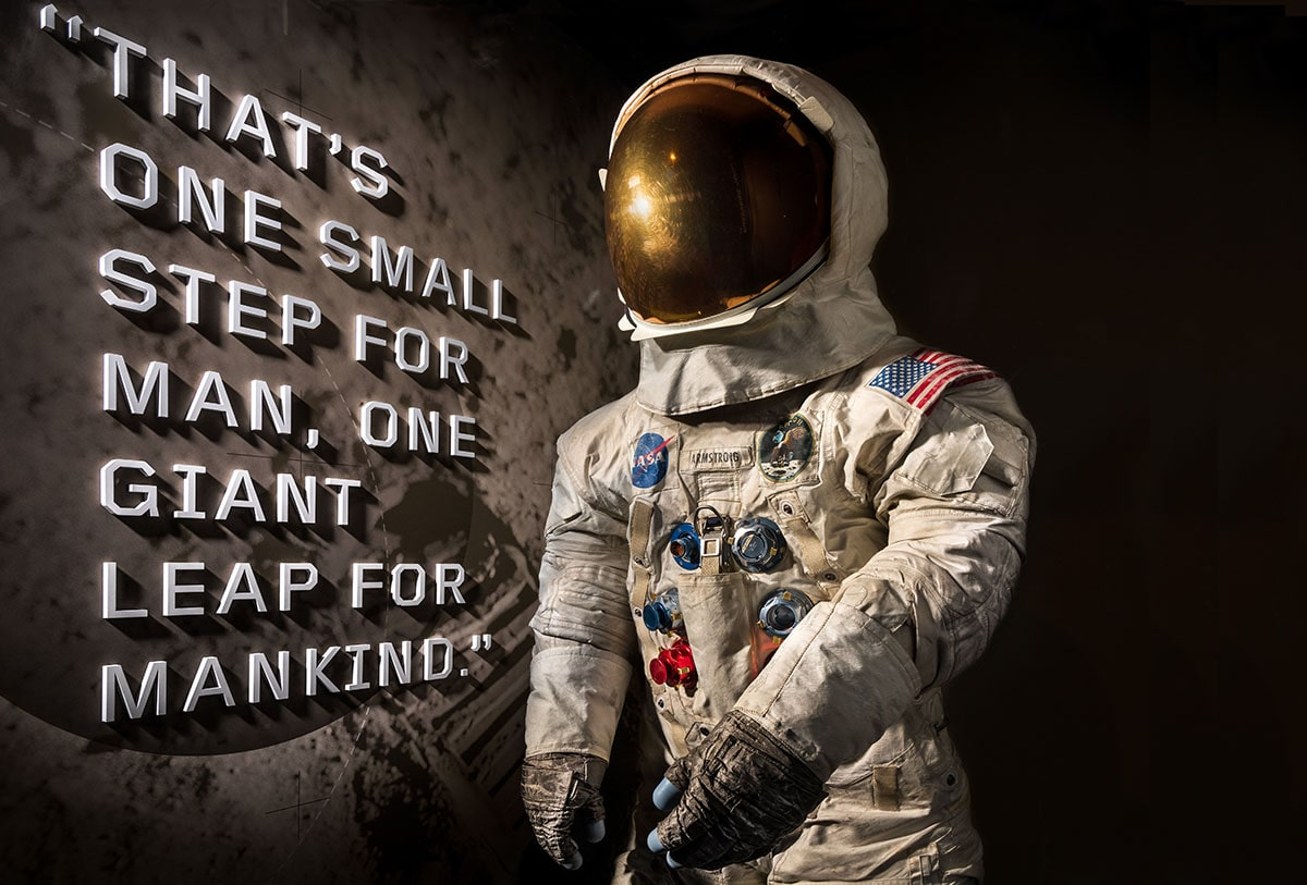 "To the left writing ""THAT'S ONE SMALL STEP FOR MAN, ONE GIANT LEAP FOR MANKIND"" next to a space suit used during the Apo"