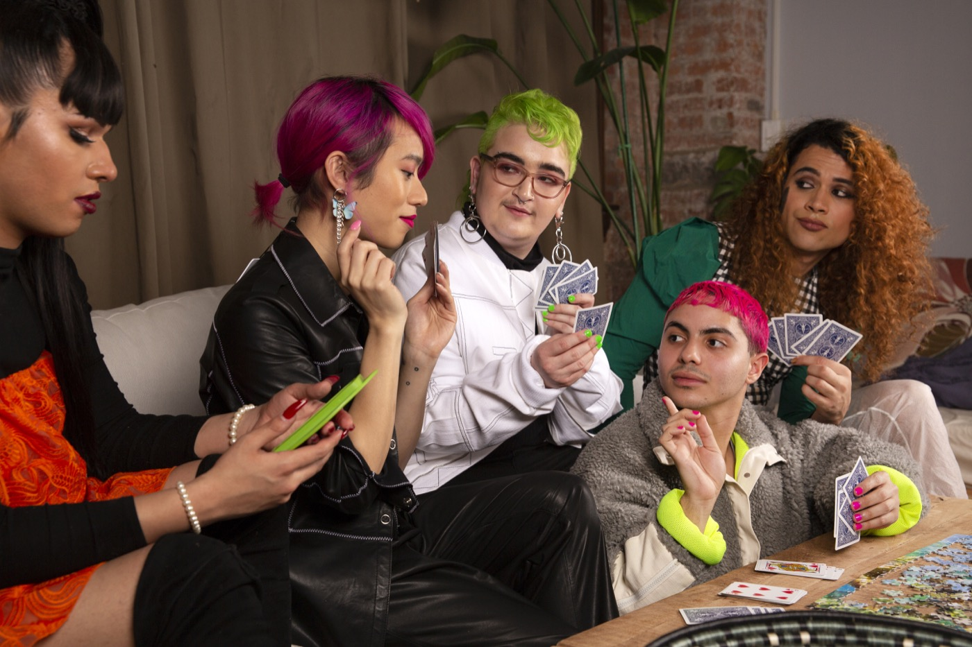 A group of friends of varying genders playing cards from the side