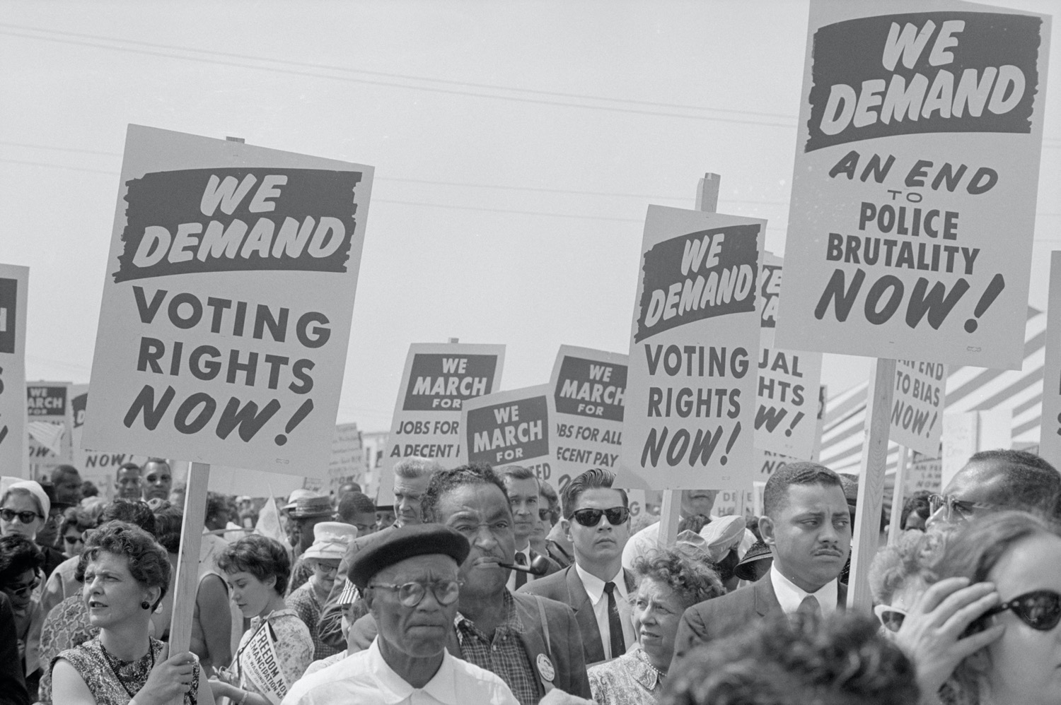 "black and white photo of people marching with signs that say ""we demand voting right now, we demand an end to police brutality, we demand voting right now"""