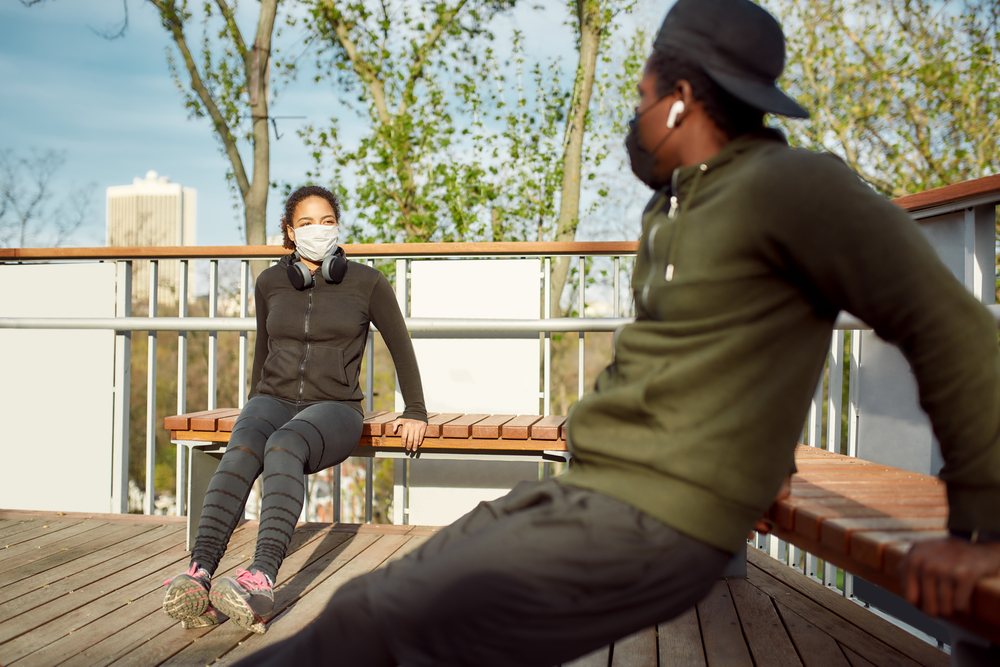 Staying fit during quarantine, couple in protective masks working out in park, oing push-ups exercises on bench