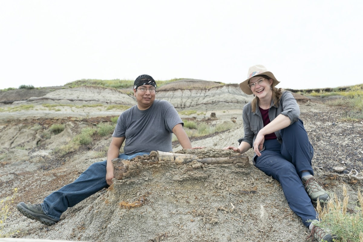 a woman and a man sit next to a fossil still embedded in the ground