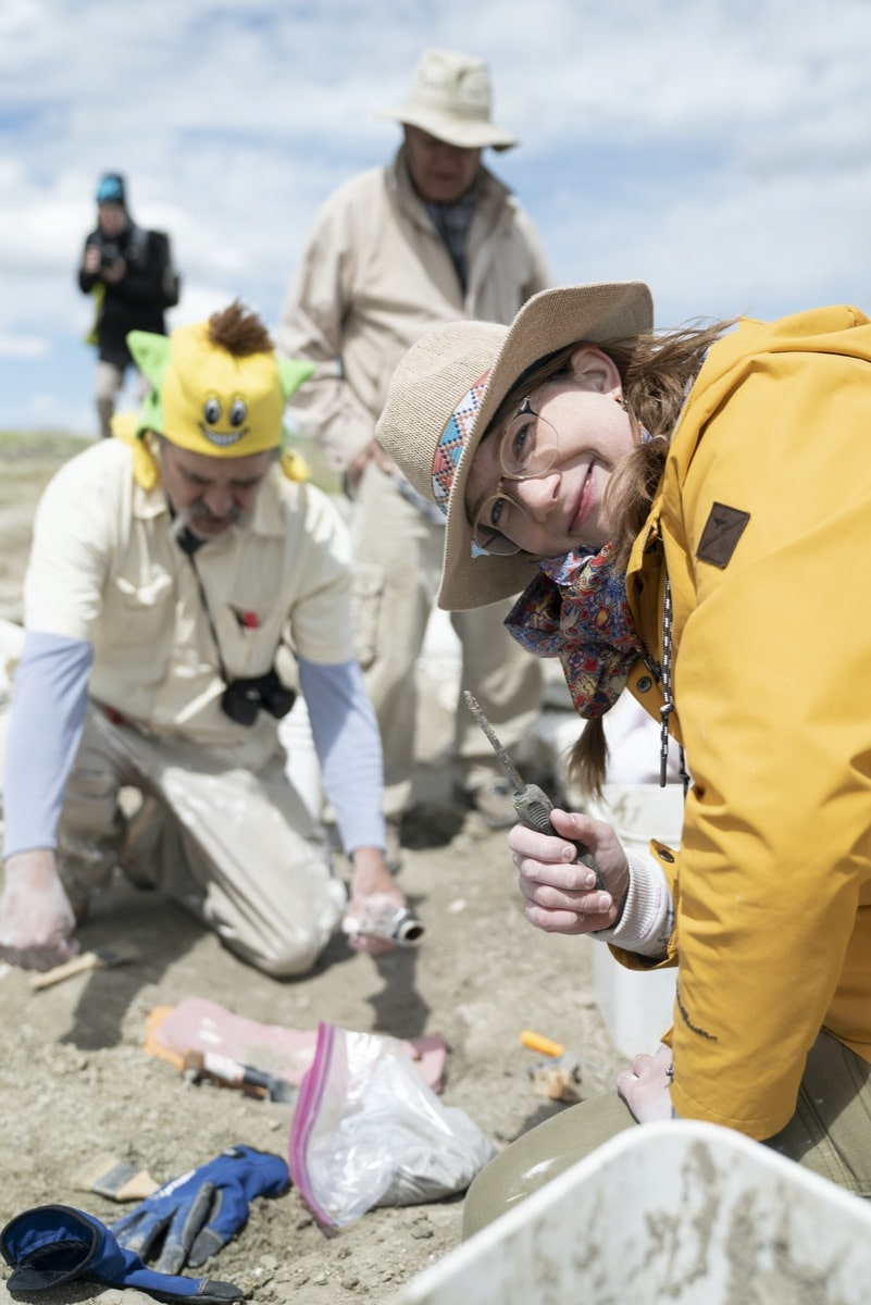 in focus a woman in a straw hat and yellow jacket holds up a digging tool, in the background are paleontologists digging at a fossil site