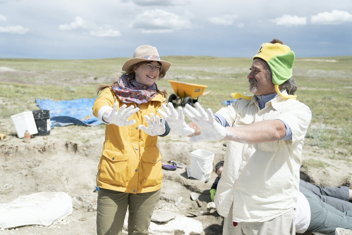 a woman and a man on a fossil dig site hold out their hands covered in white plaster
