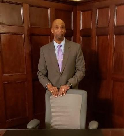 a black man in a suit stands behind a desk chair in a wood paneled office
