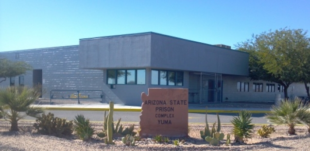 "a gray building with a sign in the shape of the state of arizona that reads ""arizona state prison complex yuma"""