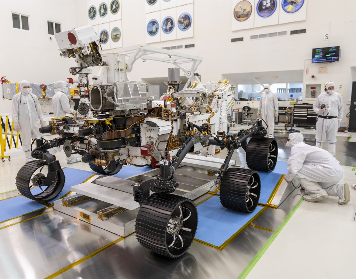 a golf cart sized robot rover with six wheels in a laboratory. researchers in white hazmat suits work on the rover