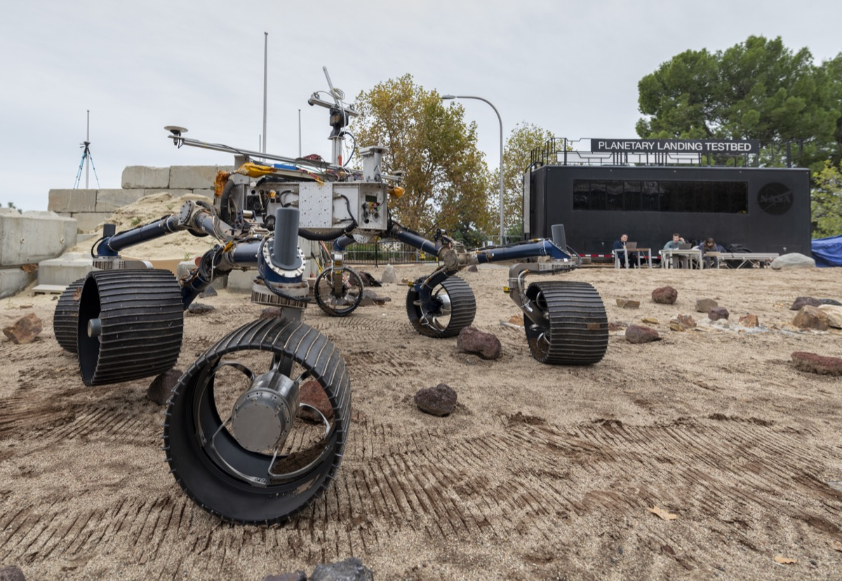 a rover robot with six large wheels out on a sandy field. you can see the wheel tracks in the sand