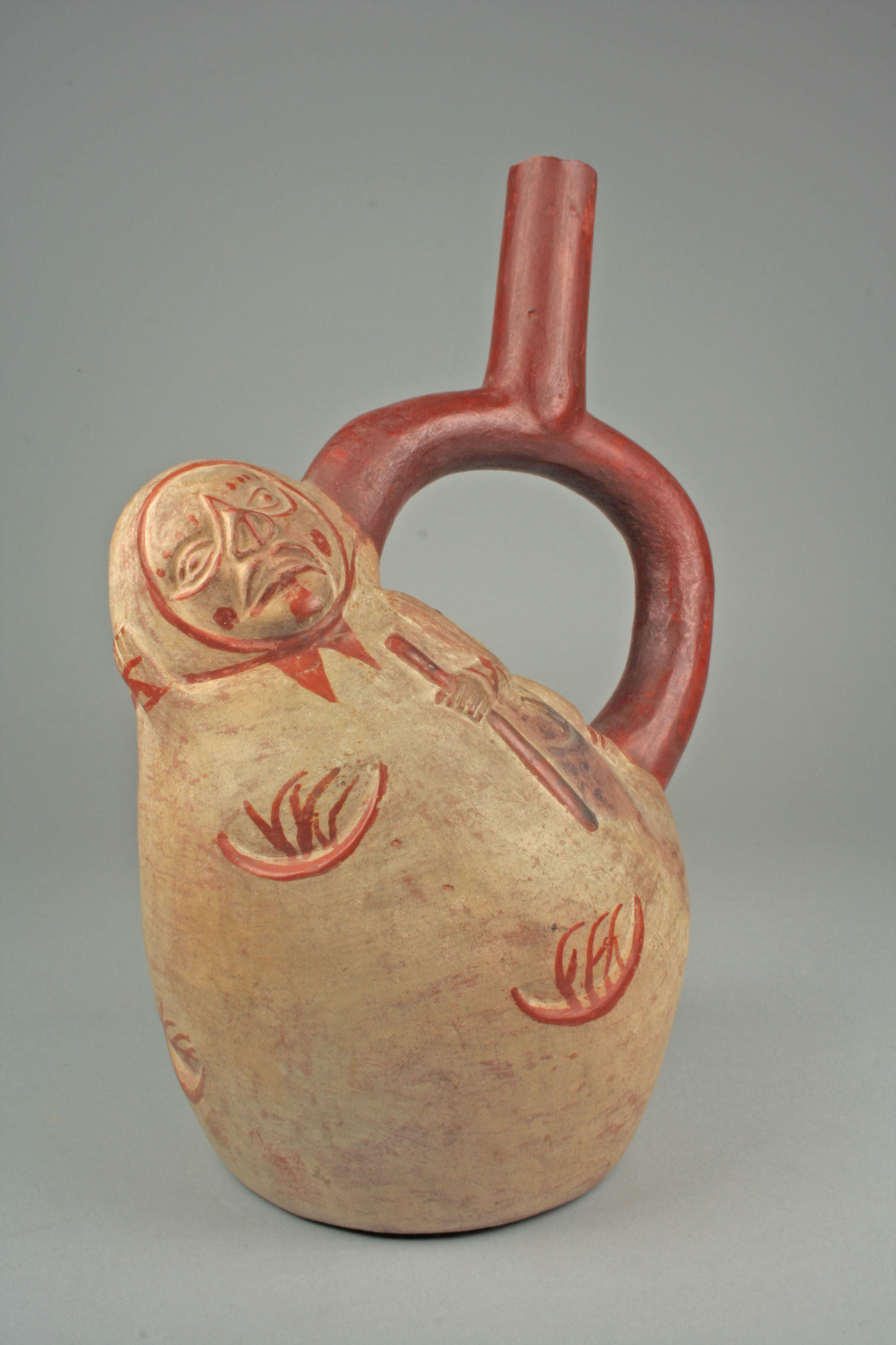"""an old ceramic jug that resembles a potato with a handle sticking out. the potato jug is anthropomorphized, with a head that has a stern looking face at the top and a hand holding a staff painted on the """"body"""""""